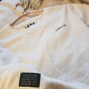 Krämvit tshirt med grön Morris logga! Storlek S lite oversized. Spårbar frakt 63kr inräknat i priset. Nypris 500kr