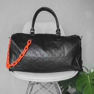 """Snygg, stilren väska inspirerad utav Louis Vuitton. Svart med orange plastkedja. Rymmer förvånansvärt mycket, kan användas som """"weekend""""-bag. Aldrig använd och har, tyvärr, bara legat i garderoben."""