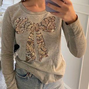 En grå sweatshirt med guldig rosett. Den är i storlek XS
